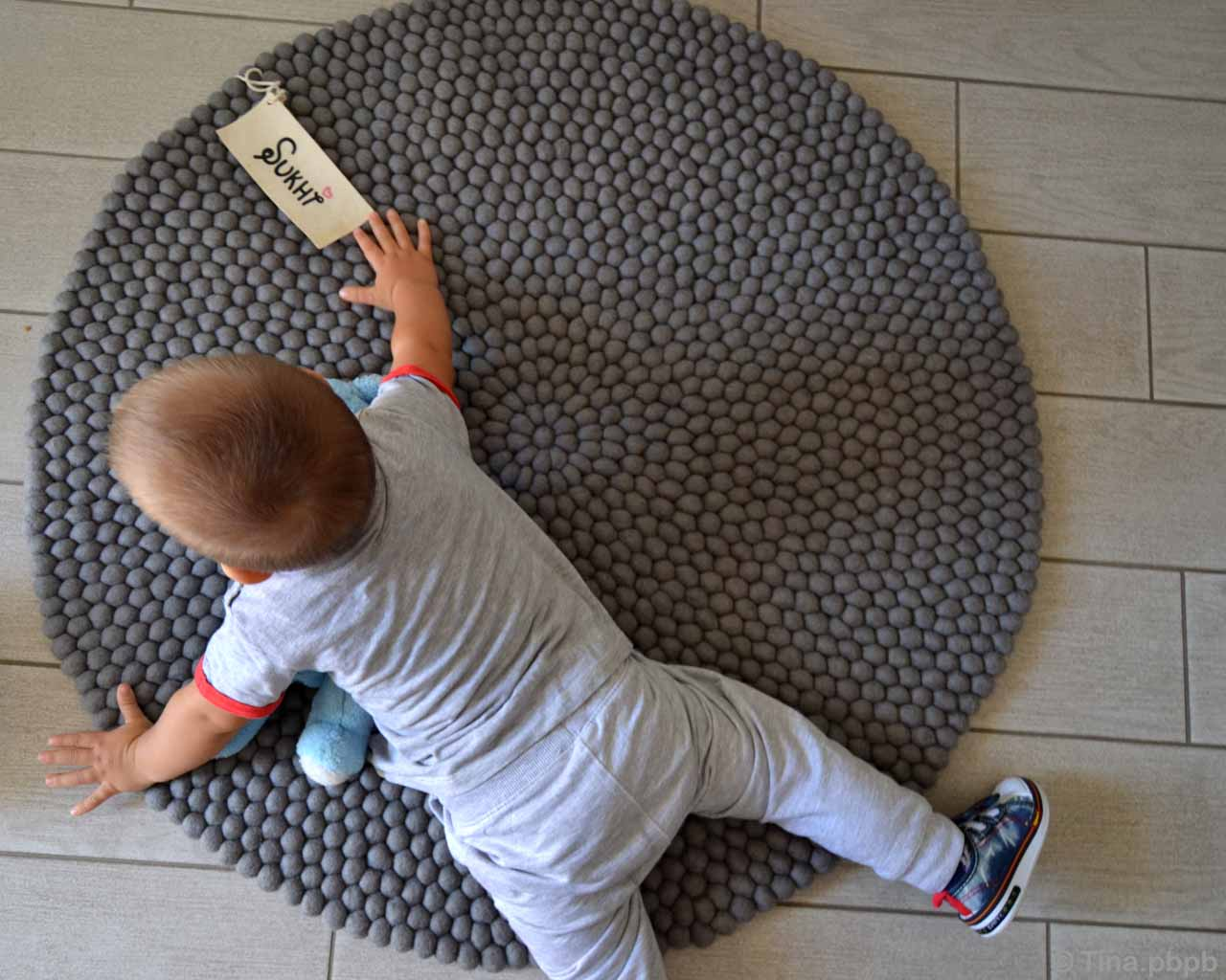 hand knotted baby playing with stuffed toy oriental rugs online