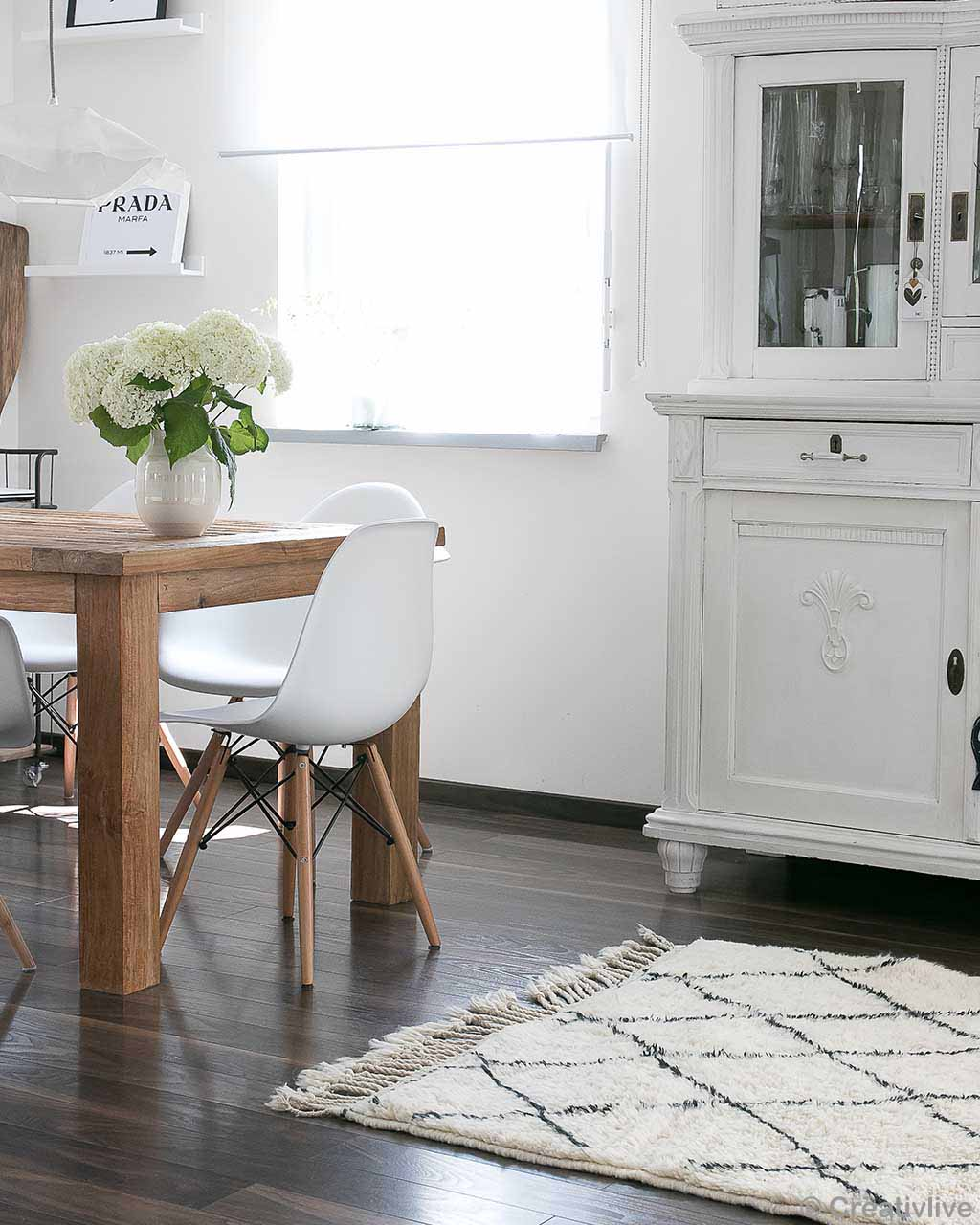 wooden table and white chairs made by moroccan rugs